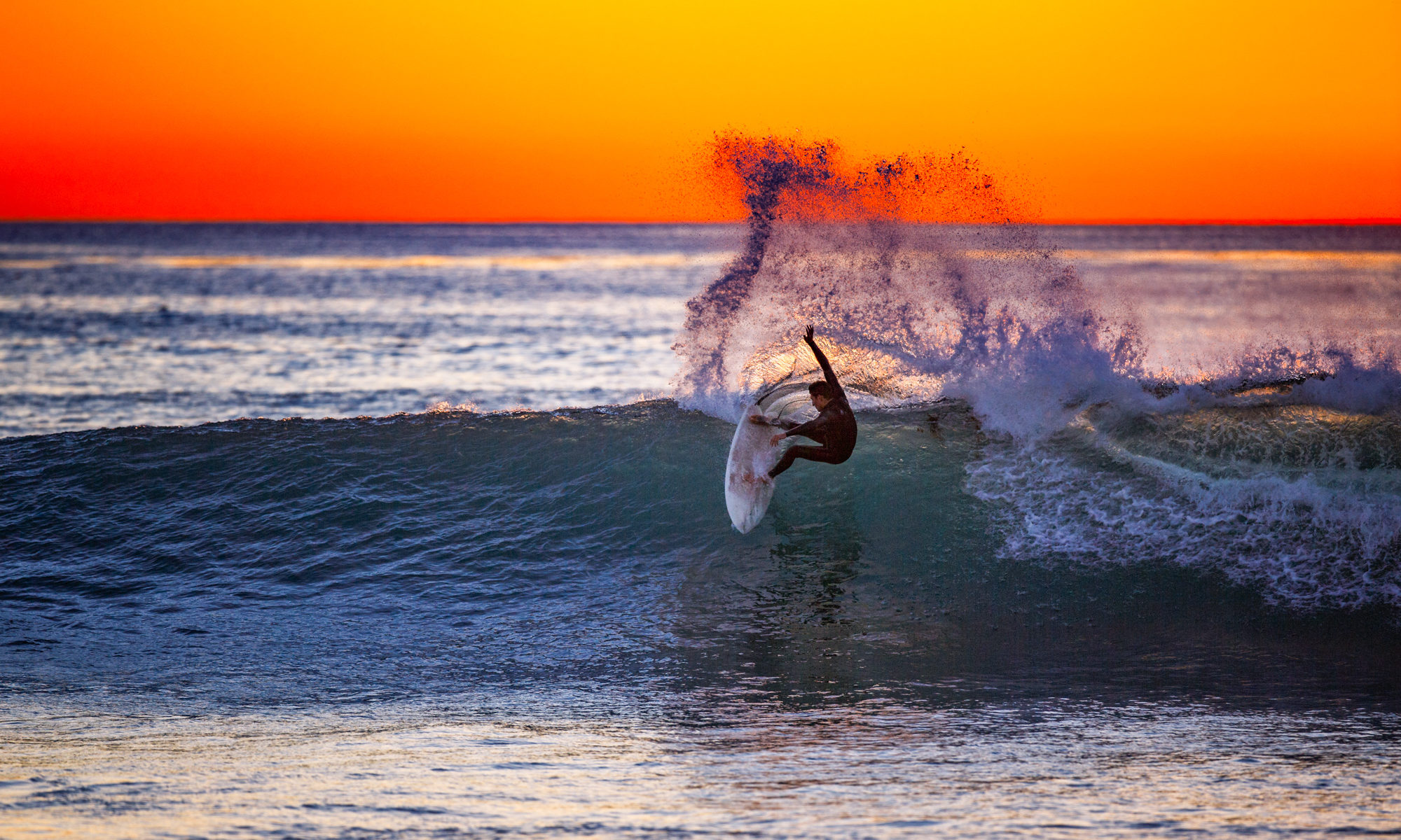 A surfer at sunset in La Jolla, California by Mark Johnson/Ironstring
